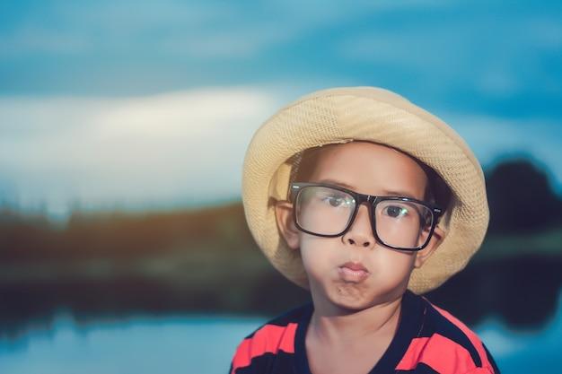 Muchacho del niño del retrato de una sonrisa en el parque de la orilla en tiempo libre. infancia feliz.