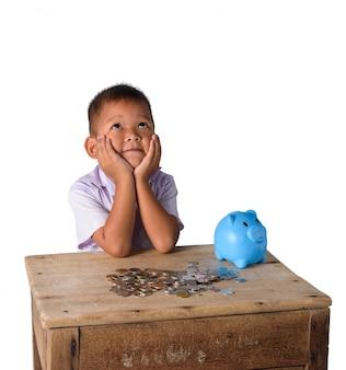 El muchacho de país asiático lindo tiene pensamiento con la hucha y las monedas aisladas en el fondo blanco
