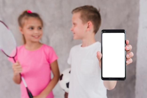 Muchacho que se coloca con la muchacha que muestra el teléfono móvil con la visualización en pantalla blanca