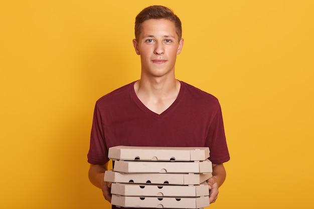 El muchacho que lleva la camiseta casual marrón que entrega las cajas de la pizza, presentando aislado en amarillo, mirando la cámara, parece serio, las hembras jovenes que trabajan como repartidor, haciendo su trabajo. concepto de personas
