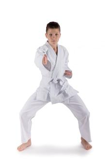Muchacho que presenta con técnicas del karate en estudio en blanco aislado