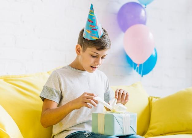 Muchacho que se sienta en el sofá que desempaqueta el regalo de cumpleaños