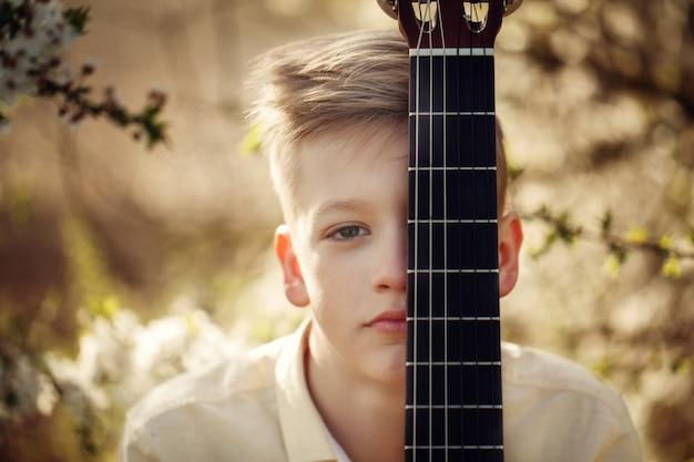 Muchacho del retrato del primer con la guitarra en día de verano.