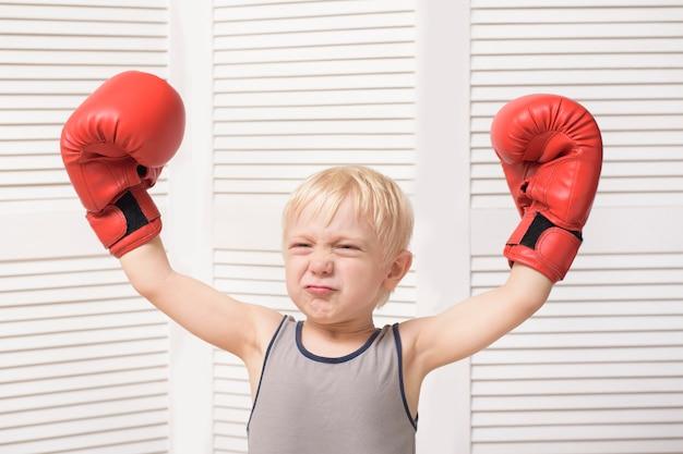 Muchacho rubio divertido en guantes de boxeo rojos. concepto deportivo