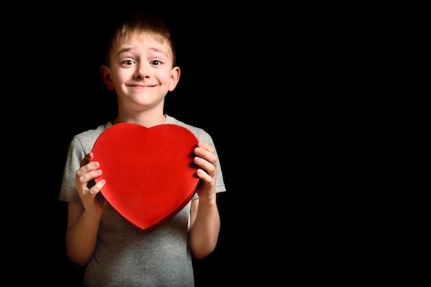 Muchacho rubio feliz que sostiene una caja roja en la forma de un corazón en fondo negro. concepto de amor y familia.