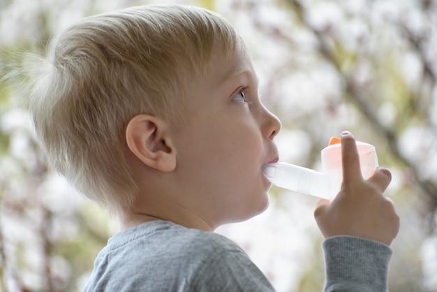 El muchacho rubio hace la inhalación en casa. árboles en flor