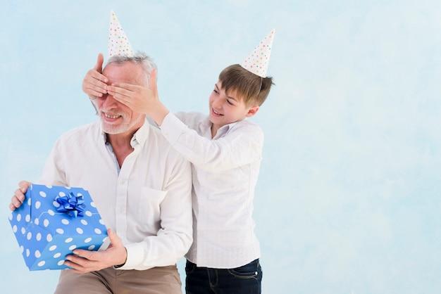 Muchacho sonriente adorable que da el regalo sorprendido a su abuelo cubriendo sus ojos contra fondo azul