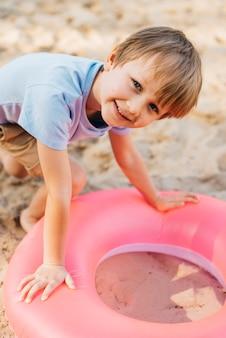 Muchacho sonriente con el anillo de la natación en la arena