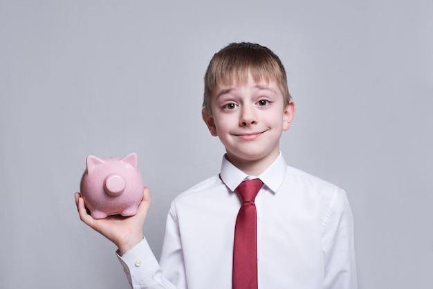 Muchacho sonriente con el cerdo rosado de la hucha en sus manos. negocio . ligero