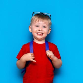 El muchacho sonriente feliz en camiseta roja con los vidrios en su cabeza va a la escuela por primera vez. niño con mochila escolar. niño
