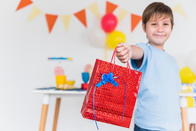 Muchacho sonriente que da el bolso rojo del regalo a alguien