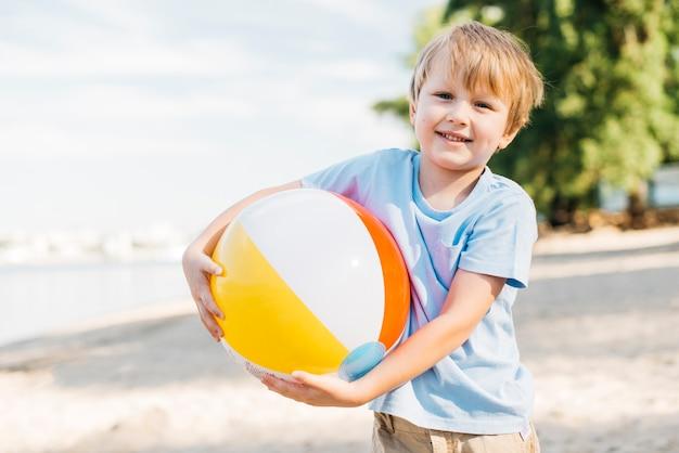 Muchacho sonriente que lleva la pelota de playa ambas manos