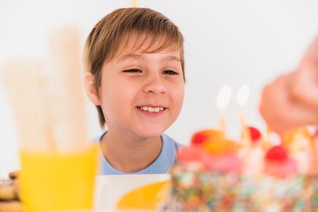 Muchacho sonriente que mira la torta de cumpleaños sabrosa con las velas ardientes