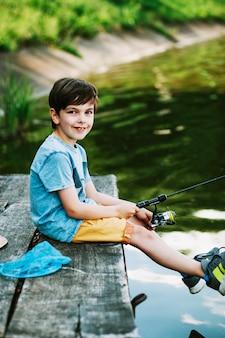 Muchacho sonriente que se sienta en el muelle que pesca sobre el lago