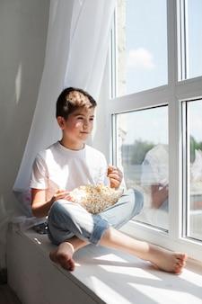 Muchacho sonriente que se sienta en el travesaño de la ventana que sostiene el cuenco de palomitas y que mira afuera