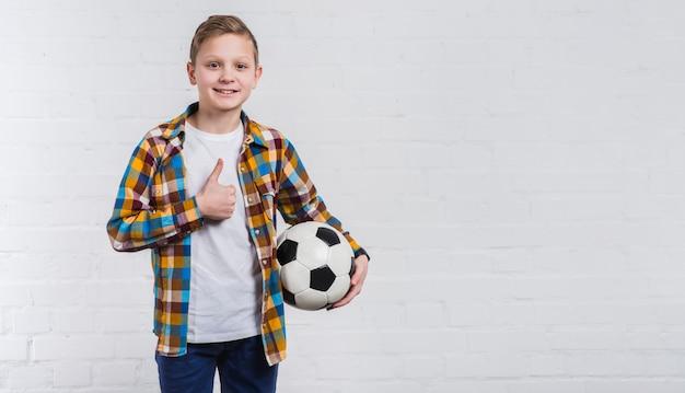 Muchacho sonriente que sostiene fútbol en la mano que muestra el pulgar encima de la muestra que se opone a la pared de ladrillo blanca