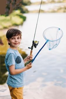 Muchacho sonriente que sostiene la caña de pescar y la red a disposición cerca del lago