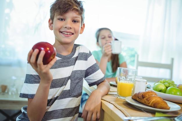 Muchacho sonriente que sostiene una manzana