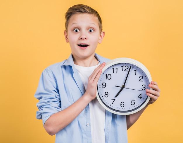 Muchacho sonriente de la sorpresa que sostiene el reloj blanco disponible que mira a la cámara contra fondo amarillo