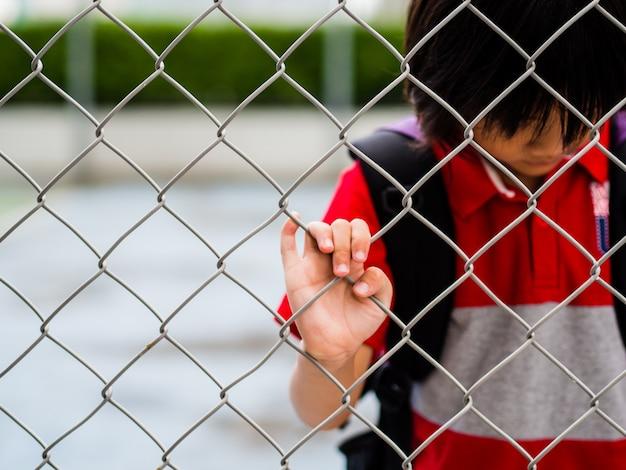 Muchacho triste detrás de la red de malla de la cerca