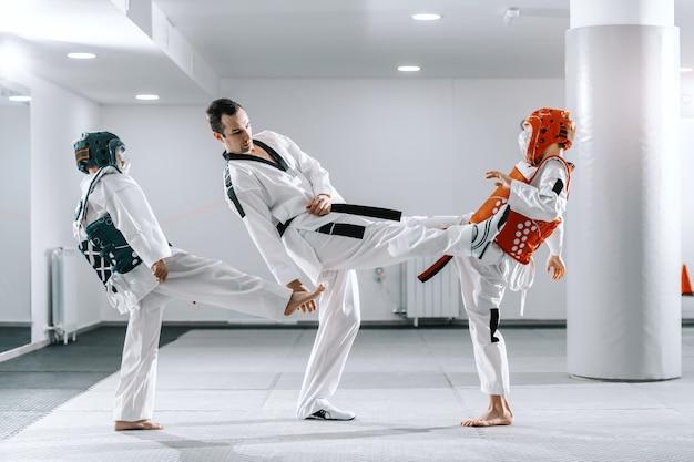 Muchachos caucásicos deportivos con entrenamiento de taekwondo en gimnasio blanco. entrenador demostrando patada.
