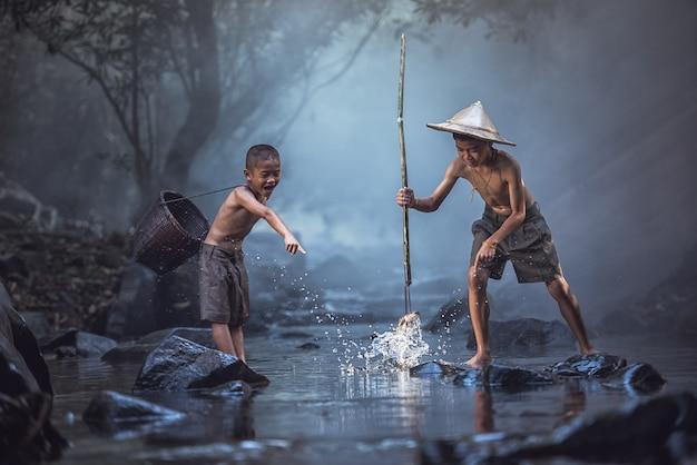 Muchachos de la pesca que pescan en el río, campo de tailandia.