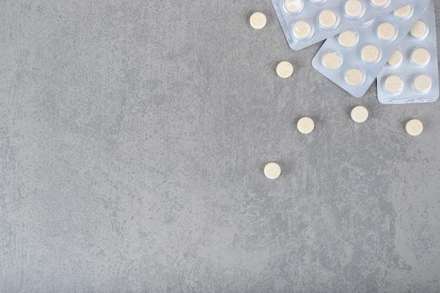 Muchas ampollas con pastillas blancas sobre superficie gris