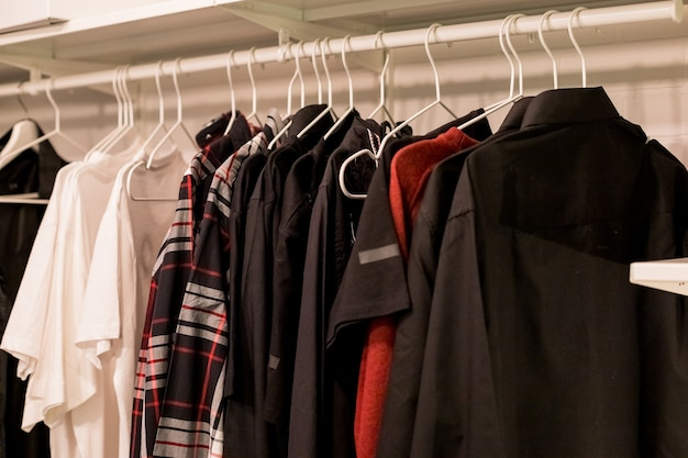 Muchas blusas, camisas en perchas en el vestidor