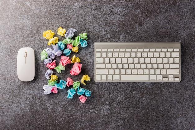 Muchas bolas de papel arrugadas con teclado de computadora