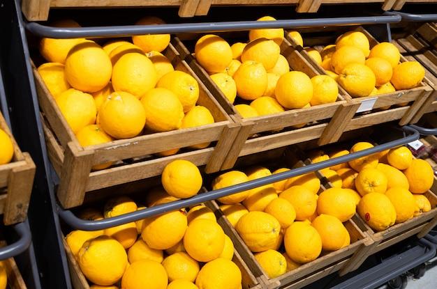 Muchas cajas de madera con limones amarillos frescos en el mostrador