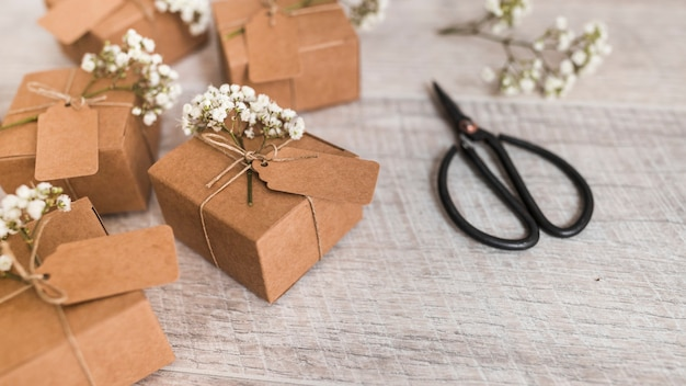 Muchas cajas de regalo atadas con cordel y flores de aliento de bebé y tijera sobre fondo de madera