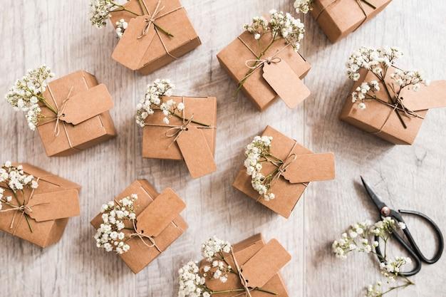 Muchas cajas de regalo de boda con tijera sobre fondo de madera