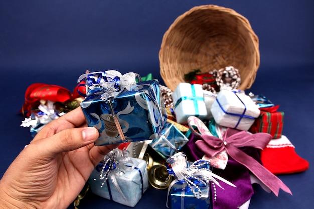 Muchas cajas de regalo y decoraciones. canasta navideña con fondo azul.