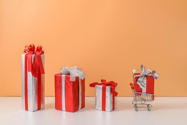 Muchas cajas de regalo con lazo de cinta roja y carrito de compras o carrito
