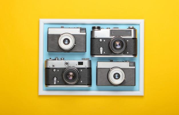 Muchas cámaras retro en superficie amarilla con marco de fotos