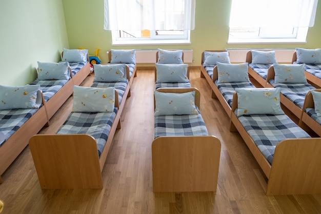 Muchas camas pequeñas con ropa de cama fresca en la guardería preescolar interior de la habitación vacía para una cómoda siesta de los niños.