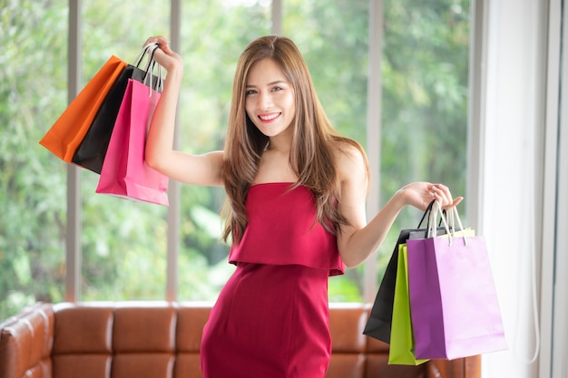 Muchas chicas son adictas a las compras como ella. ella es hermosa en vestido rojo, y sosteniendo b compras