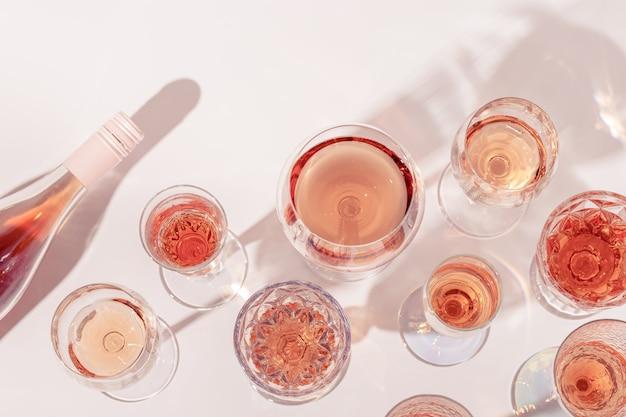 Muchas copas de vino rosado y botella de vino rosado espumoso