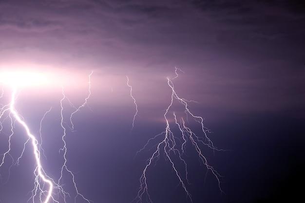 Muchas descargas de relámpagos brillantes en el cielo tormentoso bajo fuertes nubes de lluvia púrpura