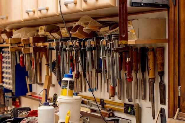 Muchas diversas herramientas viejas que cuelgan en una pared del granero.