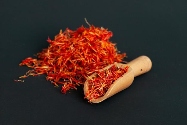 Muchas especias de azafrán picante con una espátula de madera para especias