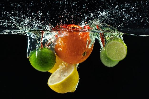Muchas frutas salpican en el agua.