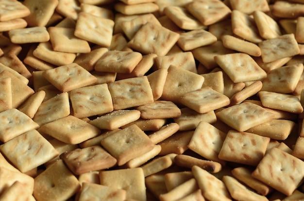 Muchas galletas pequeñas tienen forma cuadrada. un patrón de una galleta de sal amarilla. imagen de fondo con pastelería salada.