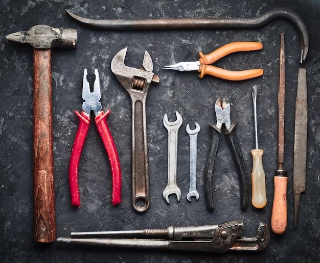 Muchas herramientas de trabajo sobre una mesa de hormigón negro. pinzas, lima, alicates, chatarra, martillo, llave inglesa, destornillador. vista superior. endecha plana.