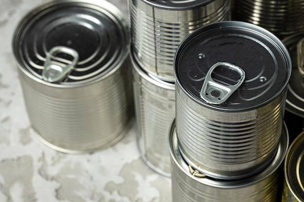 Muchas latas con comidas como carne y pescado sobre la mesa, alimentos conservados, de cerca