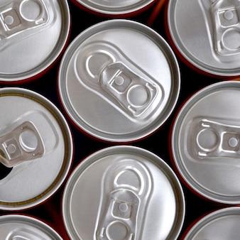 Muchas latas de refrescos o envases de bebidas energéticas. muchas latas recicladas hechas de aluminio y preparadas para la reproducción.