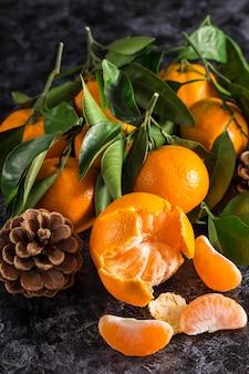 Muchas mandarinas naranjas con hojas verdes sobre fondo oscuro. conos y rodajas de mandarina peladas