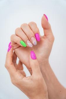 Muchas manos de manicura de color brillante tienen diferentes manchas en rosa