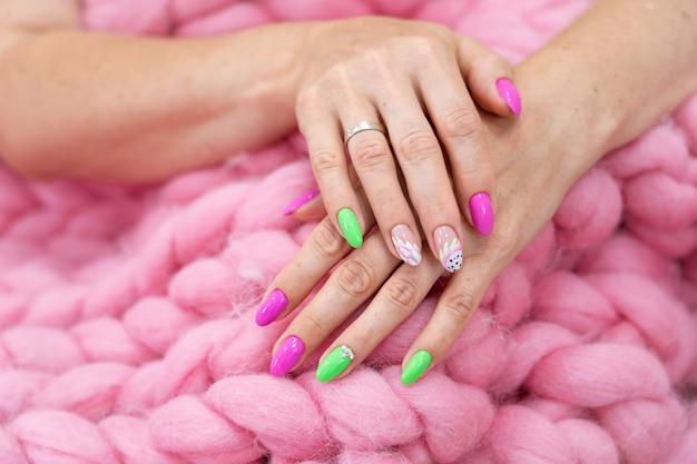 Muchas manos de manicura de color brillante tienen diferentes manchas