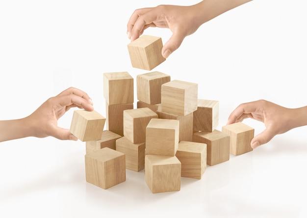 Muchas manos que juegan la caja de madera en aislado.